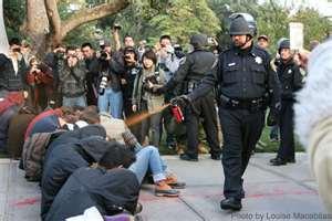 Lt. John Pike of University of California Davis pepper sprays mace into eyes of demonstrators